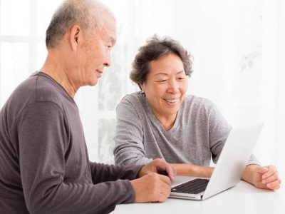 happy Senior Couple Using Laptop in living room