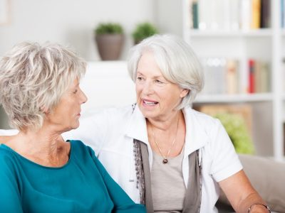 Two senior women chatting in the living room